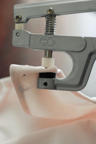 La pose d'un snap sur une aile. De bas en haut on a: presse, capuchon, le tissu de l'aile, socket ou stud, presse.